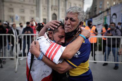 Un aficionado con la camiseta del Boca Juniors y otro con la camiseta del River Plate, se abrazan luego de despedir los restos de Diego Armando Maradona en el velatorio de la capital bonaerense, este jueves en la Plaza de Mayo en Buenos Aires, Argentina.