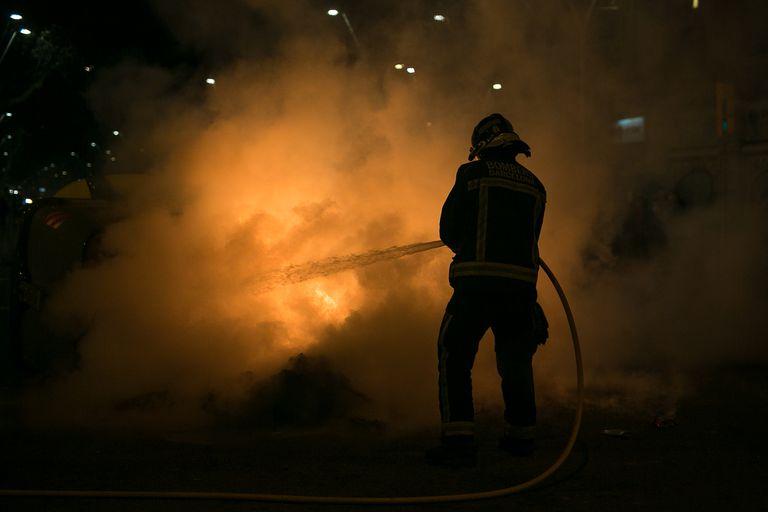 Un bombero intenta apagar uno de los contenedores incendiados durante una manifestación en apoyo a Pablo Hasél, en Barcelona