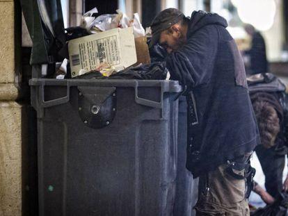 Dos personas buscan comida en un contenedor en Barcelona.