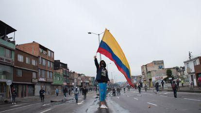 Un manifestante agita la bandera colombiana durante los enfrentamientos con la policía antidisturbios en una protesta contra el proyecto de ley de reforma tributaria propuesto por el Gobierno