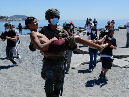 Un militar español lleva en brazos a un menor después de que haya entrado a nado en Ceuta, este miércoles.