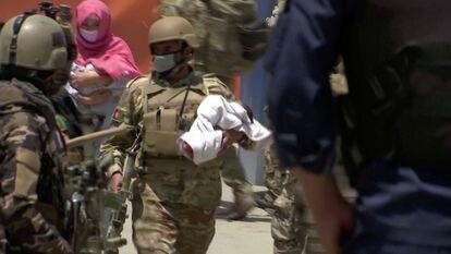 Un agente traslada a un bebé del hospital de Dasht e Barchi, en Kabul, tras el ataque del pasado 12 de mayo.