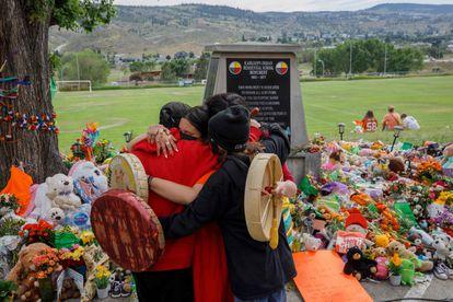 Cree Nation people hug in front of a memorial honoring the deceased minors in Kamloops.