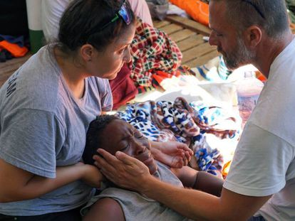 Dos sanitarios atienden a una migrante en el 'Open Arms', este domingo.