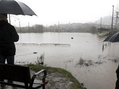 Vecinos de Hernani, observan el campo de rugby Landare, anegado por el desbordamiento del río Urumea.