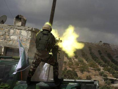 Combatiente rebelde sirio de una facción favorable a Turquía dispara una ametralladora pesada durante las maniobras de entrenamiento para la inminente operación turca contra las milicias kurdas del norte de Siria.