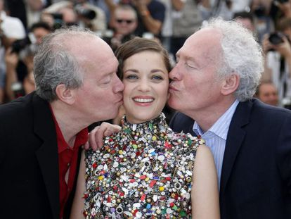 Los hermanos Jean-Pierre (derecha) y Luc Dardenne besan a la actriz francesa Marion Cotillard durante el pase gráfico de la película 'Deux Jours, Une Nuit' (Dos Días, una noche) en la 67ª edición del Festival de Cannes.