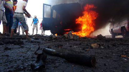 Yemeníes se acercan a un vehículo incendiado en Adén.