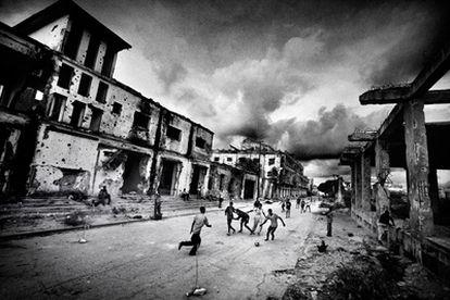Un grupo de niños juega al fútbol en una calle de Mogadiscio entre edificios en ruinas por los enfrentamientos armados.  Esta fotografía forma parte de <i>Somalia en el fin del mundo</i>, reportaje fotográfico galardonado con el Premio Ortega y Gasset de Fotografía 2009, publicado en el <i>Magazine</i> de <i>La Vanguardia</i> del 1 de febrero de 2009.