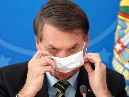 El presidente Bolsonaro se ajusta la mascarilla, durante un acto en Brasilia. / REUTERS