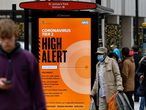 Pedestrians walk past Tier 2 Coronavirus information displayed on an electronic advertising board at a bus stop in central London on December 14, 2020. - The majority of England's 55 million population are under Tier 2 or 3 restrictions, depending on local infection rates. London -- Britain's capital and driving force of the UK economy -- is currently in Tier 2, meaning pubs where food is served and restaurants can open, obeying social distancing rules. But in Tier 3 areas, hospitality venues have to close except for takeaways. (Photo by Tolga Akmen / AFP)