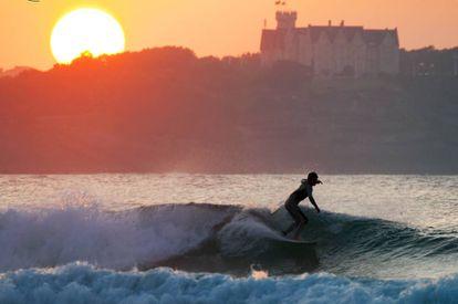 Surfeando en la playa de Somo con el Palacio de la Magdalena al fondo.