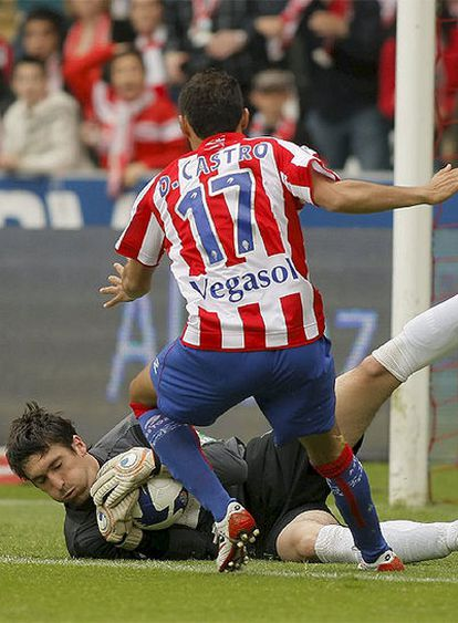 El guardameta del Málaga Goitia atrapa el balón en el césped ante la llegada de Diego Castro.