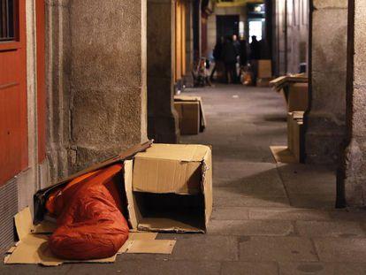Una persona sin hogar durmiendo en los soportales de la plaza Mayor de Madrid.
