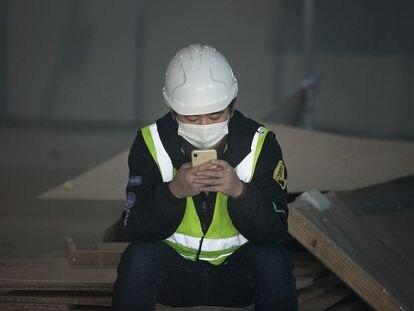Un trabajador consulta su móvil en Barcelona, el pasado febrero.