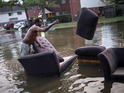 Vince Ware traslada sus sofás desde su casa inundada en Houston, Texas.