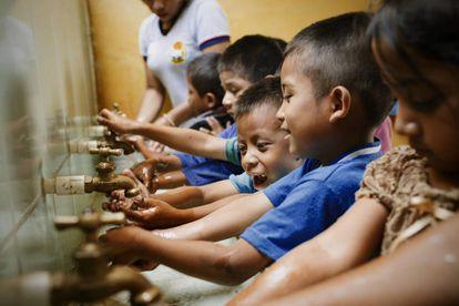Unos alumnos de la escuela rural de Los Vados (Guatemala) se lavan las manos antes de clase.