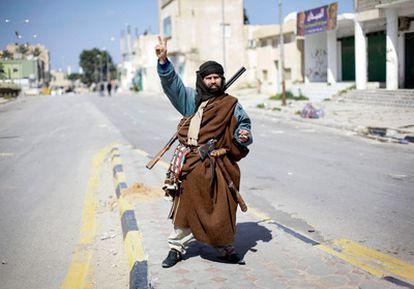 Un residente de Zawiya (50 kilómetros al oeste de Tripoli), que forma parte del levantamiento contra Gadafi, empuña sus armas en medio de la calle de la ciudad.
