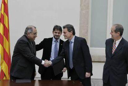 Artur Mas y Joaquim Nadal se saludan tras la firma del acuerdo de investidura en el Parlament.