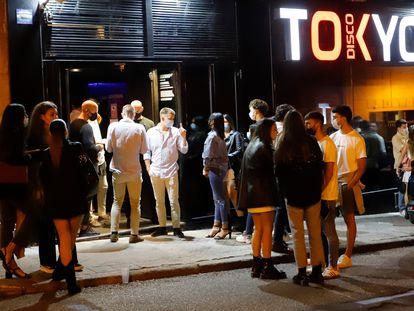 Varios grupos de jóvenes esperan en el exterior de un establecimiento durante la primera noche de la reapertura del ocio nocturno con restricciones en Vigo, el 1 de julio.