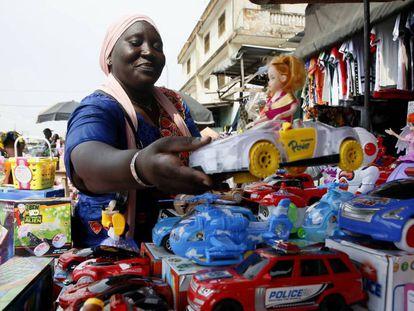 Una vendedora callejera en el pulmón económico marfileño, Abiyán, ordena su mercancía de Navidad.