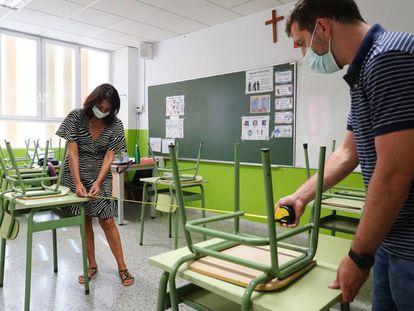 Dos docentes miden la distancia de seguridad entre las mesas de los alumnos.