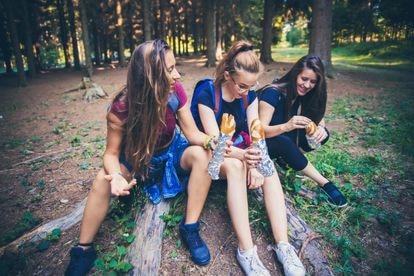 Un grupo de chicas comen durante una ruta de senderismo.