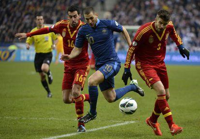 Benzema intenta marcharse de Busquets y Piqué.