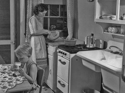 Una mujer prepara la comida en la cocina junto a su hijo.