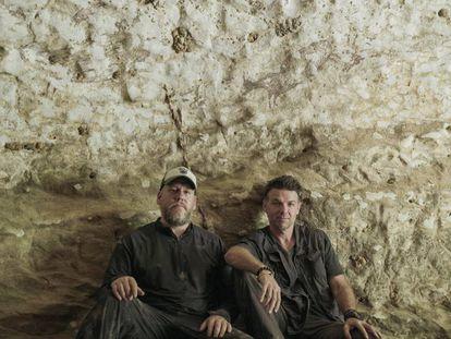 Los arqueólogos Maxime Aubert y Adam Brumm posan bajo la obra de arte figurativo más antigua del mundo, en la isla de Célebes (Indonesia).