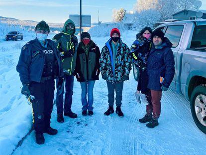 Gary Bath, segundo por la izquierda, y Lynn Marchesault, tercera por la izquierda, en el puesto fronterizo de Beaver Creek, Alaska.