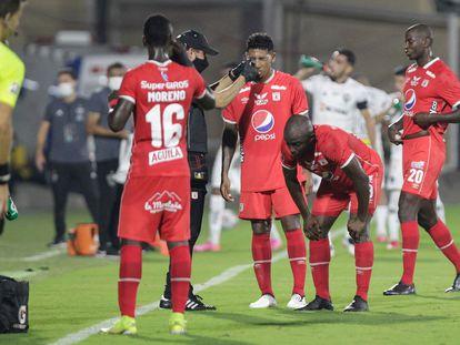 Un asistente ayuda a los jugadores del América de Cali afectados por los gases lacrimógenos durante su partido de Copa Libertadores contra Atlético Mineiro, en el estadio Romelio Martínez de Barranquilla.