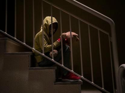 Un niño en una escalera en penumbra.