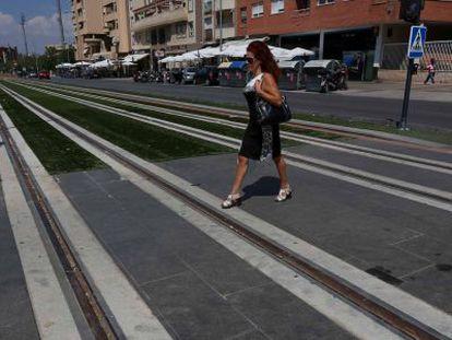 Una mujer cruza por las vías del metro de Granada, en el barrio del Zaidín.