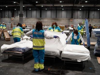 Trabajadores sanitarios preparan las camas para recibir a enfermos de coronavirus en el hospital temporal montado en Ifema, este domingo.