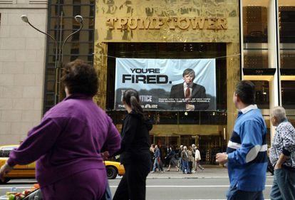 Peatones pasan en 2004 delante de un cartel del programa de Donald Trump El aprendiz, colgado de la Trump Tower, de su propiedad, en Nueva York.