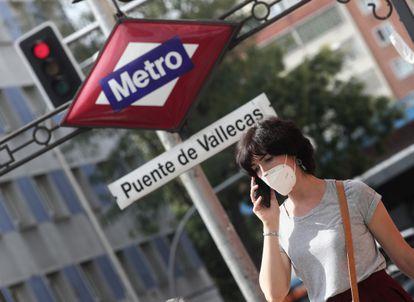 Una mujer pasea al lado del metro de Puente de Vallecas.