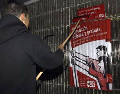 Un joven coloca un cartel informativo de la huelga general de toda la enseñanza pública y privada concertada, que dará comienzo mañana con el paro de tres jornadas convocado en las enseñanzas medias por el Sindicato de Estudiantes (SE) en protesta por la LOMCE.