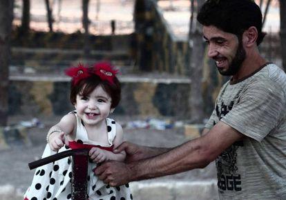 Un hombre juega con una niña en el segundo día del 'Eid el-Adha' o fiesta del sacrificio, la mayor festividad de la comunidad musulmana.