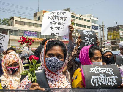 Miembros de una organización de derechos laborales sostienen pancartas y flores para rendir homenaje a las víctimas en el lugar donde estuvo el edificio Rana Plaza en las afueras de Dacca, Bangladés, 24 de abril de 2021, octavo aniversario del desastre.