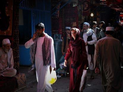 Una mujer transita entre hombres por las calles del bazar Mandawi de Kabul.