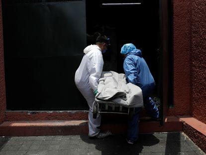 Trabajadores de una funeraria transportan un cuerpo al crematorio en Ciudad de México este lunes.