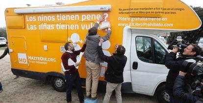 El presidente de Hazte Oír, Ignacio Arsuaga, coloca pegatinas en la caravana tránsfoba.