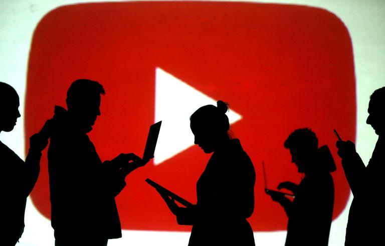 Varias personas revisan sus dispositivos electrónicos frente al logo de YouTube.