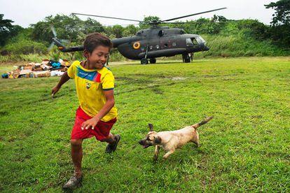 """Luis Napa y su perro """"Pelusa"""" juegan en el estadio de Pedernales, Ecuador, mientras un helicóptero del Ejército deja ayuda humanitaria."""