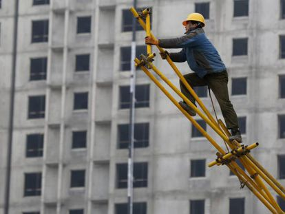Un obrero trabaja sobre un andamio para encofrado en las obras de construcción de un edificio. EFE/Archivo