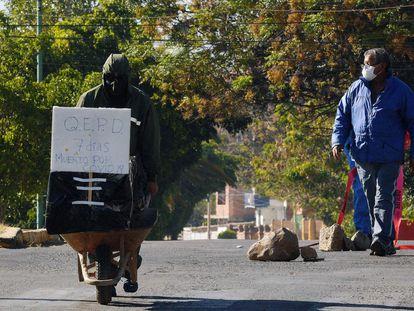 El trabajador de una funeraria empuja una carreta con el ataúd de un fallecido por coronavirus, el pasado mes de julio en Cochabamba.