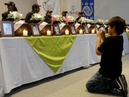 El niño colombiano Juan Andrés Córdoba hace una fotografía de los restos de su padre, durante la ceremonia de entrega de los cadáveres de 17 personas desaparecidas desde hace más de diez años a sus familiares, el martes en Medellín.