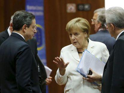 Merkel habla con Monti (derecha) y Draghi, el viernes en Bruselas.