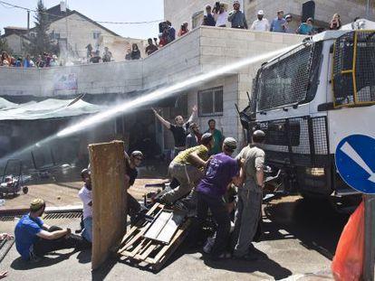 Agentes israelíes lanzan agua contra colonos del asentamiento de Beit EI, el miércoles.